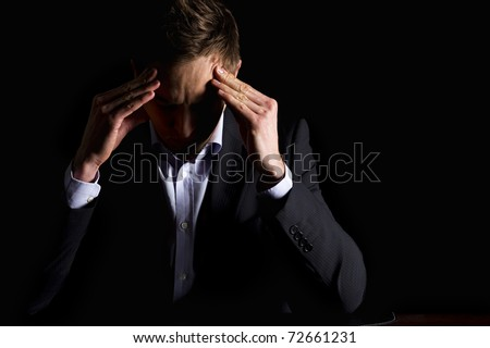 Low-key portrait of modern serious business person in dark suit sitting at office desk looking down and contemplating with both hands resting at head, isolated on black background with copy-space.
