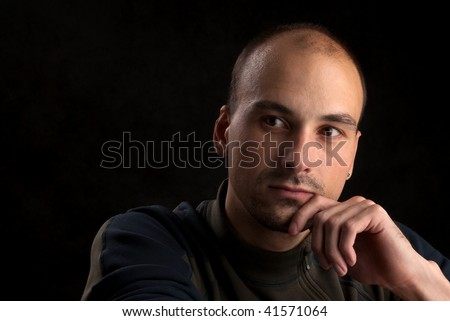 Low-key portrait of pensive young man