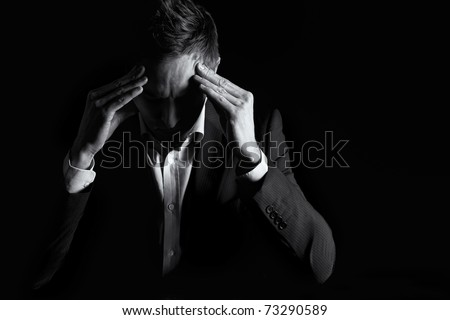 Low-key portrait of worried business person in dark suit sitting at office desk looking down and contemplating with both hands resting at head, black & white conversion.