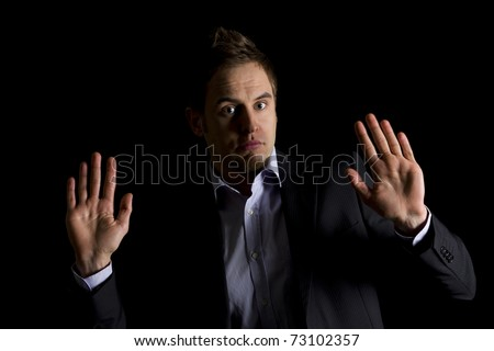 Low-key portrait of young clueless business person in dark suit sitting at office desk being confused, isolated on black background with copy-space.
