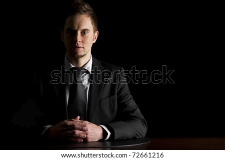Low-key portrait of young serious businessman in dark suit sitting at office desk looking straight, isolated on black background with copy-space.