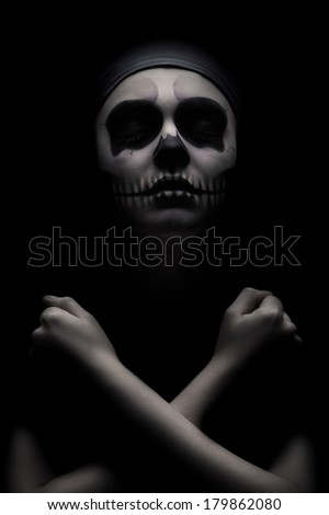 Stock Photo Low key portrait of young woman with skull make-up.