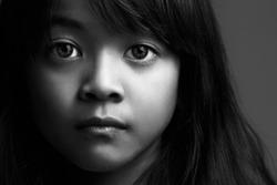 Low key shot of little asian girl in black & white