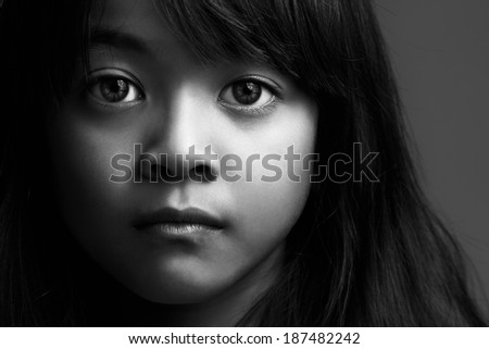 Low key shot of little asian girl in black & white