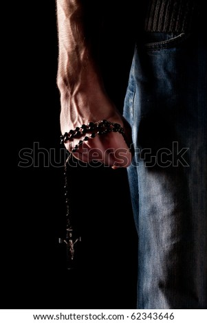 Low key shot or a man's arm gripping a rosary