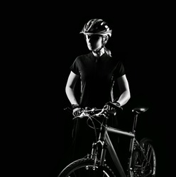 Low key silhouette of a girl cyclist with  her bicycle on black background