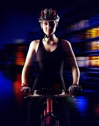 low key silhouette of a girl cyclist  with her bicycle on city lights background