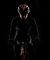 low key silhouette of a male cyclist riding his bicycle isolated on black
