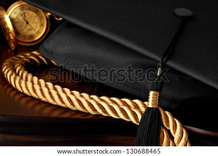 Low key still life with graduation cap and tassel, honor cords, and pocket watch on elegant wood furniture.  Macro with shallow dof.  Selective focus on tassel.