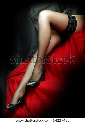 Low key studio shot beautiful slim legs in black nylons on a red background. Great image for calendar.