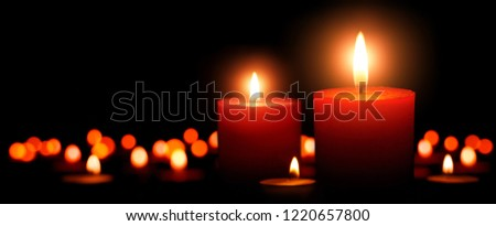 Low-key studio shot of elegant advent candles with two flames in the foreground, black background with defocused flames
