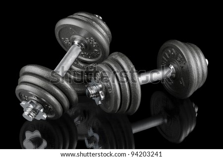 Low-key studio shot of two heavy dumbbells on black with reflections