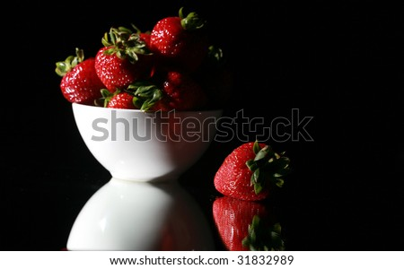 Low Key Studo Shot of fresh strawberries in a white bowl on a mirror for reflections Isolated on black