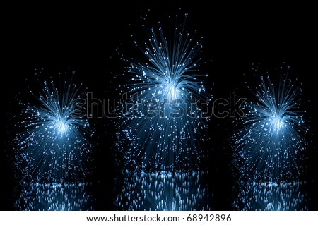 Low level angle capturing three blue groups of illuminated fiber optic light strands against a black background and reflecting into the foreground. - stock photo