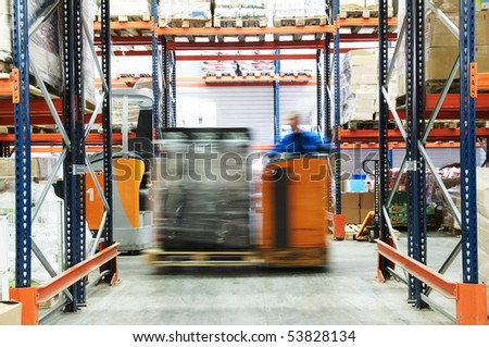 low level picker loader with driver moving in a warehouse