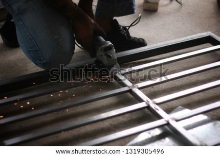 Low light image a Worker using electric wheel grinding on steel structure in garage. #1319305496