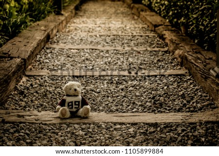 Low light of Teddy bear on the railroad tracks. Sad and alone feeling concept.