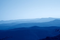 low mountains in haze. untouched mist nature away from man toned in trendy pantone Classic Blue color of the Year 2020