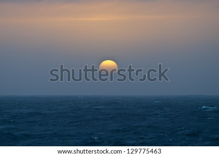 Low on the horizon, the sun shows as a beautiful ball of color.  Antarctica has some of the most beautiful sunrises and sunsets on Earth.