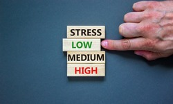 Low or high stress level symbol. Businessman chooses the wooden block with words low stress. Words stress low medium high. Beautiful grey background. Low or high stress level concept. Copy space.