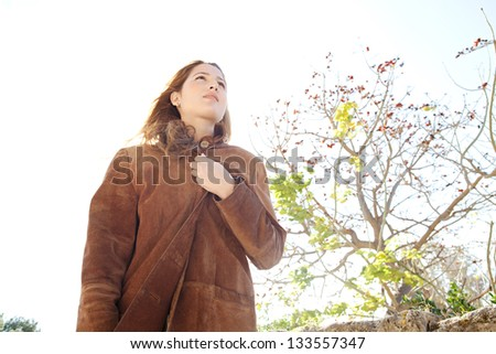 Low perspective portrait of a young attractive woman wearing a leather coat and covering herself during a sunny winter day in a park.