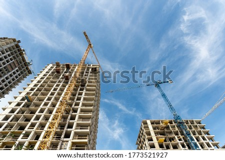 Low perspective view angle of building under construction with tower crane equipment against blue sky and copy space background. Concept of new unfinished multistory