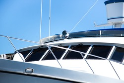 Low perspective view of front bow and navigation bridge with communication equipment of expensive mega yacht with black tinted windows and chrome metal railings on white fiber glass hull with blue sky