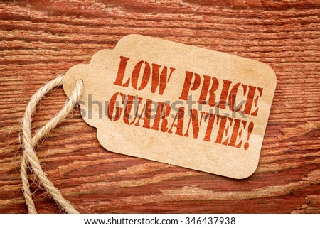 low price guarantee - sign on paper price tag against a rustic barn wood #346437938