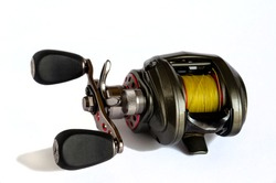 Low Profile Baitcasting Reel. Close-up of a fishing reel with yellow fishing line. Isolate on a white background. Selective focus. Front view