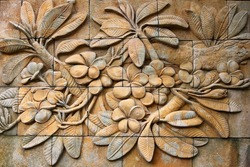 Low relief cement Thai style handcraft of plumeria or frangipani flowers  on wall