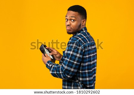 Low Salary. Discontented Black Man Holding Wallet With Cash Money Looking At Camera Standing On Yellow Studio Background. Foto stock ©