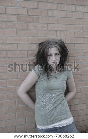 Low saturated photo of runaway girl against brick wall background