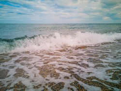 low sea wave brakes on the beach
