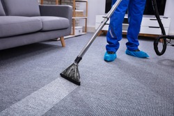 Low Section Of A Male Janitor Cleaning Carpet With Vacuum Cleaning In The Living Room