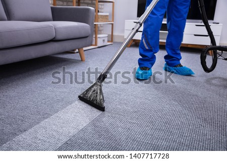 Low Section Of A Male Janitor Cleaning Carpet With Vacuum Cleaning In The Living Room Stockfoto ©