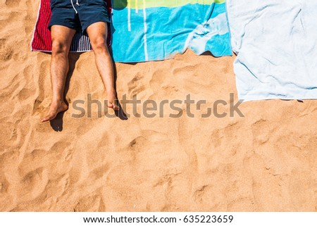 low section of a man laying on a towel in the beach #635223659