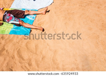 low section of a man laying on a towel in the beach #635924933
