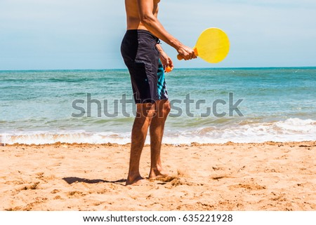 low section of a man playing racket on the beach #635221928