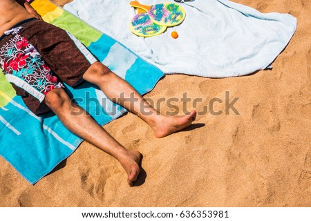 low section of a man relaxing on a colorful beach towel #636353981