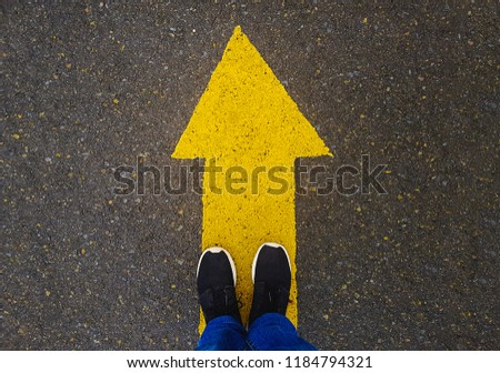 low section of a man standing on yellow arrow on asphalt ground  #1184794321