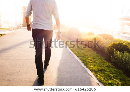 low section of a man walking in a sunny bright day #616425206