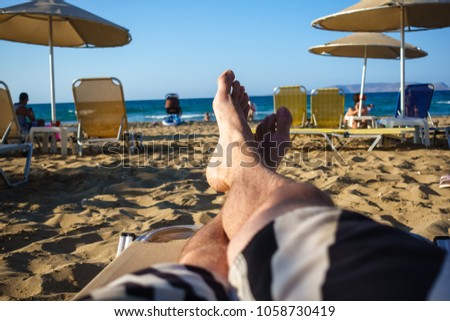 Low section of barefoot man relaxing on sandy beach lounge chair #1058730419
