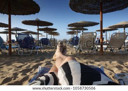 Low section of barefoot man relaxing on sandy beach lounge chair #1058730506