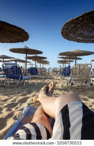 Low section of barefoot man relaxing on sandy beach lounge chair #1058730515