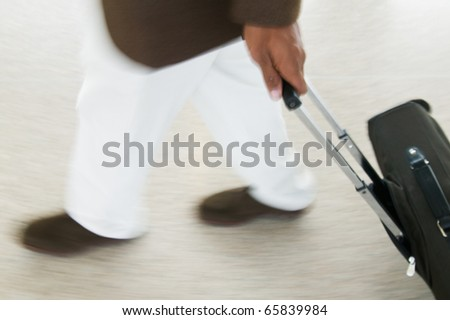 Low section of businessman with luggage