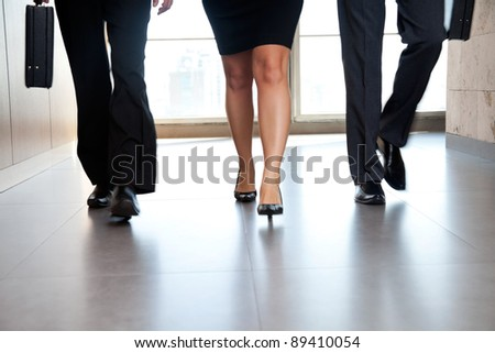 Low section of businesspeople walking along the office corridor