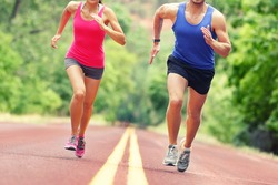 Low section of determined man and woman running on country road. Young couple is in sports clothing. They are representing their healthy lifestyle.