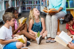 Low section of female teacher with smiling children reading books in library
