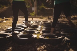 Low section of friends running over tyres during obstacle course in boot camp