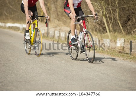 Low section of male athletes riding bicycles on a country road